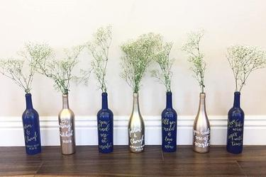 Painted wine bottles with modern calligraphy used as centerpieces for bridal shower and wedding cocktail tables.