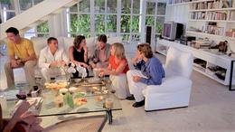 Photo of a group of adults sitting on white sofas in a living room social setting.