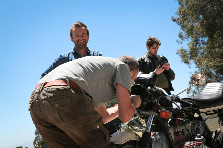 group of men working on motorcycle laughing blue sky