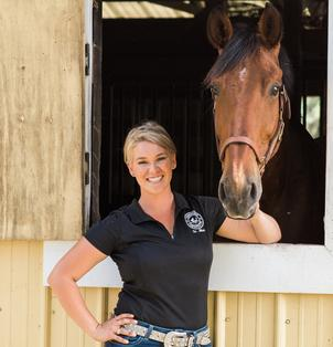 Dr. Jillian with tall bay horse in stall window