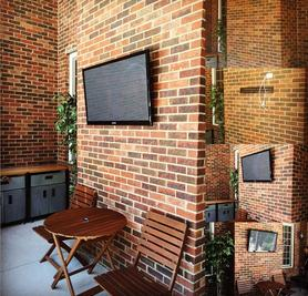 TV mounted to unwired brick wall on an outdoor patio, Carolina Custom mounts, Professional TV mounting service, Charlotte NC