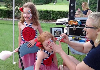 Face Painting-Two girls getting patriotic designs at a company picnic.