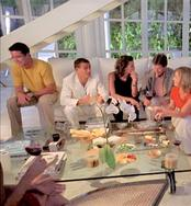 House party showing guests sitting around on white sectionals talking to each other.