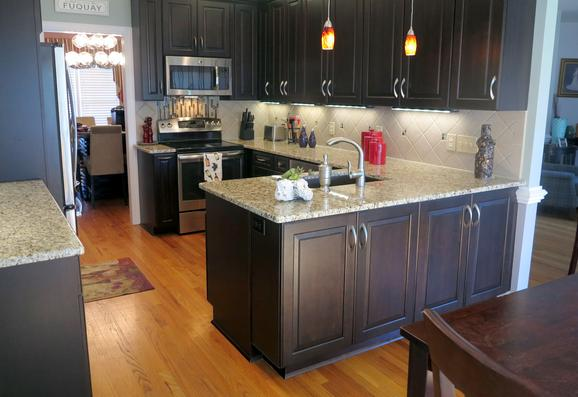 Dark cabinets accented by light granite countertops