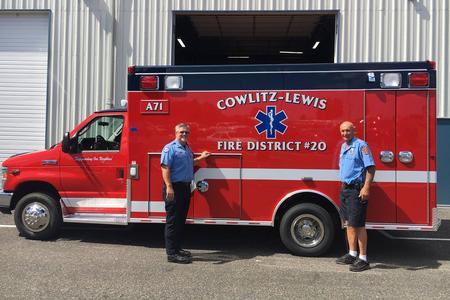 Two first responders standing in front of a fire department ambulance.