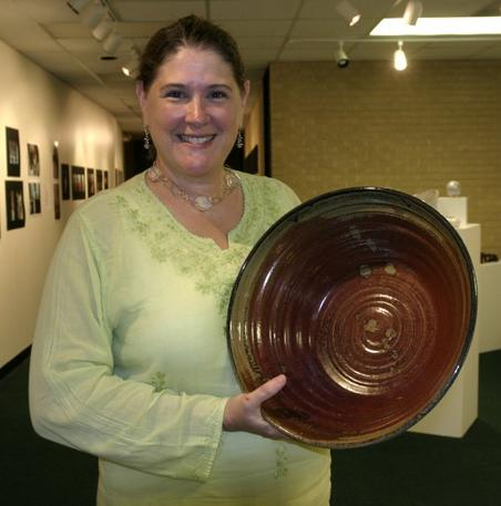 Janice Hill holding a large bowl she made. Hand-thrown, hand-glazed stoneware and porcelain pottery.