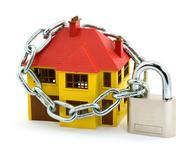 A yellow house with a red roof and a chain and lock around it