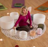 Blond woman sitting on the floor surrounded by singing water bowls creating water sound with a mallet.