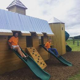 Picture of Big and Little Hank coming down the slides on Hank's Wooden Barn and Silo Play structure