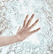 Woman's right hand touching crackled glass wall doing a Psychometric energy reading.