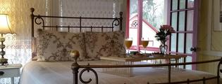 Accommodations at the Umpleby House B&B, view of room with antique iron bed and open door leading to balcony