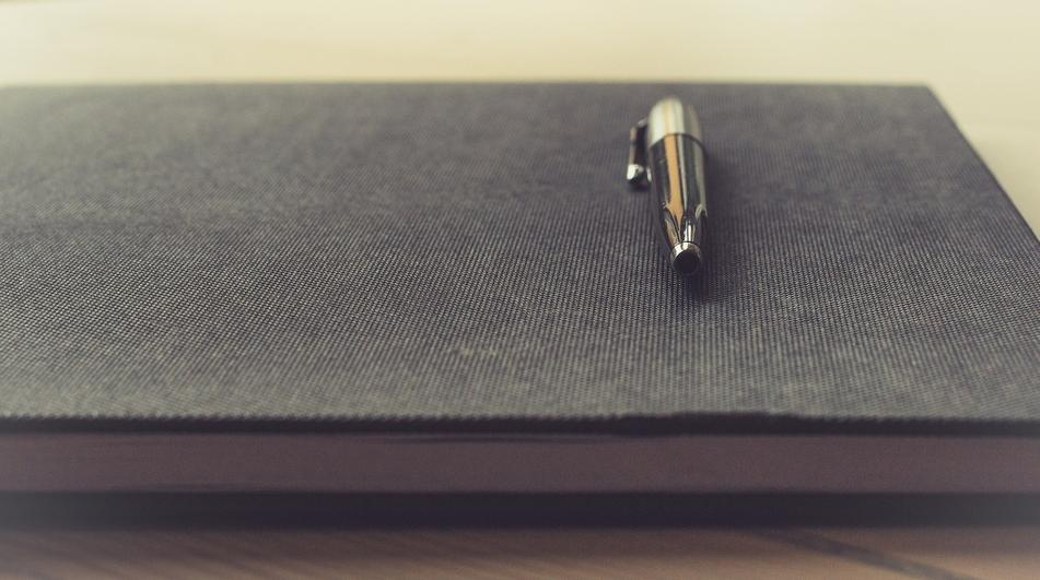 Background image of a notebook with a pen on top