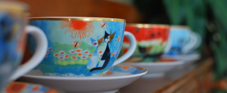 Photo of decorative tea cups on lobby shelf with cats pictured.