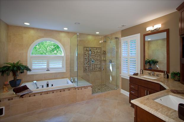 Beautiful custom tile work and Showplace cabinetry in master bathroom after remodel with frameless glass shower enclosure