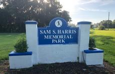 "A blue and white sign with ""Sam S. Harris Memorial Park"" in white text on it in front of a wooded area."
