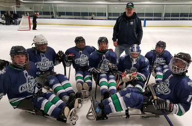 Group photo of Sno-King Thunderbirds Sled Hockey team in full uniforms on the ice rink.