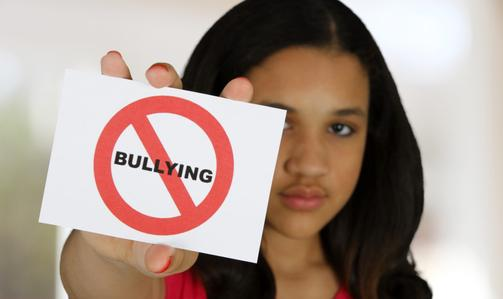 A girl showing a No Bullying sign