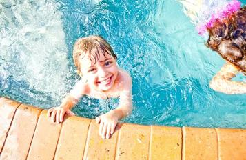 Kid in pool smiling photo