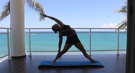 Yoga teacher practicing stretching poses for Flexibility in a balcony in front of the. Ocean Salutation to the sun for the improvement of overall body flexibility.