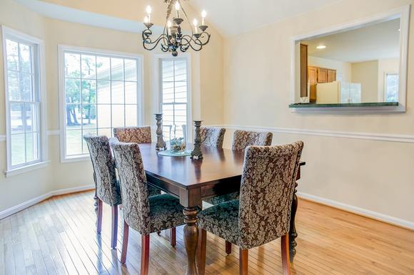This otherwise empty dining room got a fresh face with new furniture. Upholstered chairs, a large table and a centerpiece helped make the dining room in this vacant Southern Maryland home come to life!