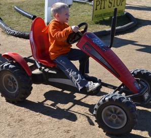 Picture of a Young boy driving a red pedal cart at Hank's PumpkinTown