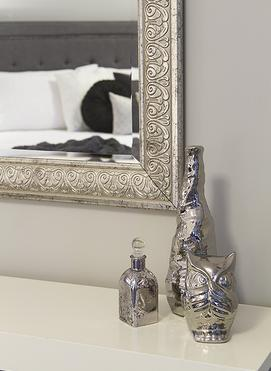 Silver owl, vase, and perfume bottle on table with silver mirror