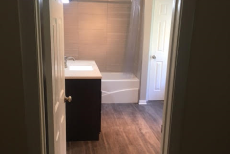 Complete bathrrom remodel. New bathtub, tile shower, sink and vanity. The toilet was moved. New plumbing and electrical. A linen closet was built and a new tile floor was laid.