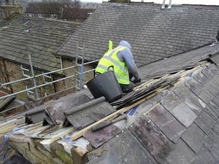 Roofer repairing tiles in Bury