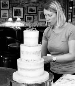 Gemma Hart owner setting up semi naked 3 tier cake