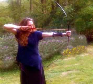 right handed, female archer with arrow pulled back in bow ready for release.