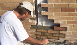 Patrick Grammatico repairing a crack in the brick wall. Brick was removed and then relayed at the Ann Arbor home.