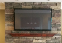 Flat screen tv mounted on stone fireplace
