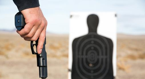 A man holding a gun at a shooting range while taking concealed carry lessons in Scottsdale, AZ