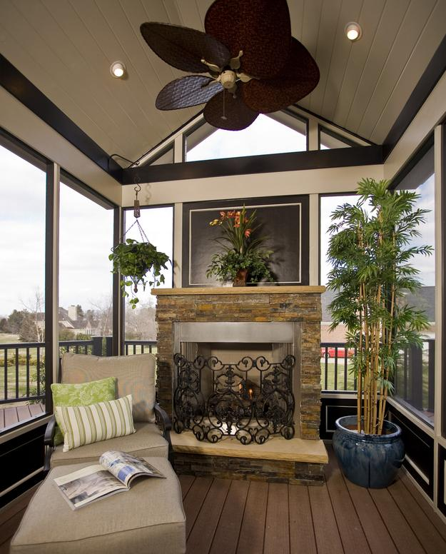 The fireplace is accented by Real Stone in this screened porch addition in North Raleigh