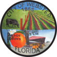 Circular logo for the city of Webster with pastures, a cow, an orange, and a building.