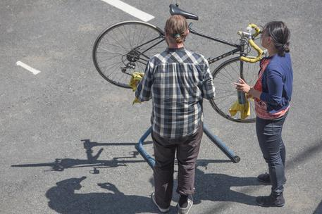 male and female working on bicycle outside in sunshine
