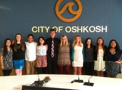 students in business casual attire in front of a City of Oshkosh wall display