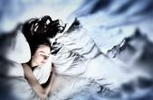 Woman sleeping in a comfy bed snuggled into white pillows.