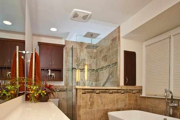 Owner's bathroom with soaking tub and custom tile shower stall after remodel