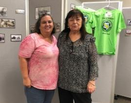 Assistant City Clerk Amy Flood and City Clerk Barbara Kane standing next to each other and smiling in front of a grey wall.