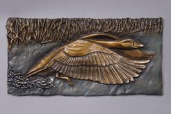 Bronze relief of a goose running along the water taking flight
