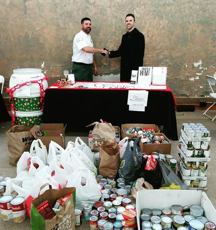 Image of two men shaking hands in front of large assortment of canned food donations.