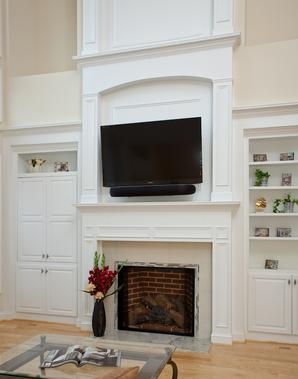 Custom fireplace with built in cabinetry in builder's spec home after remodel to make this home personalized