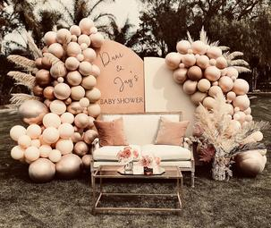 Boho baby shower backdrop with balloons half arches panmpas grass and dried palms