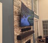 Curved flat screen tv mounted over fireplace, sound bar floating under TV. Carolina Custom Mounts
