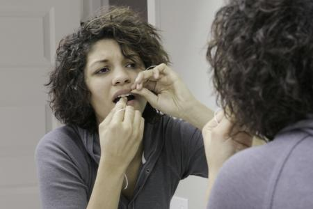 Model demonstrates the difficulties of flossing your teeth using traditional methods: messy, difficult to grip of hold the floss.
