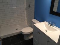 "This basement bathroom development required tearing out a portion of an existing basement development, opening the concrete, and roughing in new drain systems and water lines. This bathroom was finished using a 60"" acrylic shower base with two-tone tile."