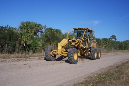 CAT grader grading a dirt road