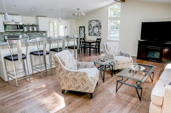 Vacant home staging includes neutral furniture in an arrangement that brings out the features of a home. This open floor plan and updated gray, white and black kitchen is accentuated by the bar stools and gray artwork.