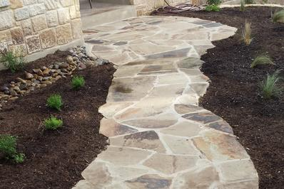 a beautiful custom San Antonio Landscape Design flagstone mortor walkway with deep black mulched beds on both sides and small mexican feather grass and shrubs planted on both side of the landscaping job in San Antonio